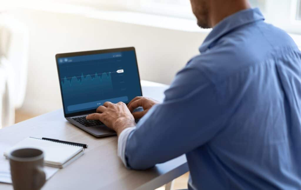 Businessman Working With Financial Analytics Or Trading Online On Laptop In Office
