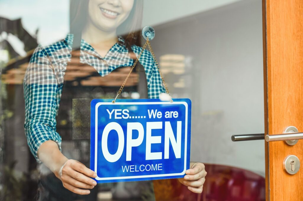 Closeup hand of Asian young woman setting open sign at the shop glasses for welcome the customer