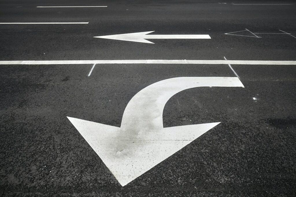 Turn or go straight street signs on asphalt.